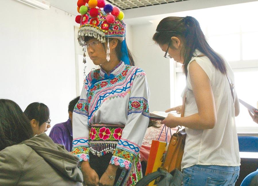 中央民族大學內,一名身著民族傳統服飾的彝族女孩正在學院辦理新生入學手續。(中新社資料照片)