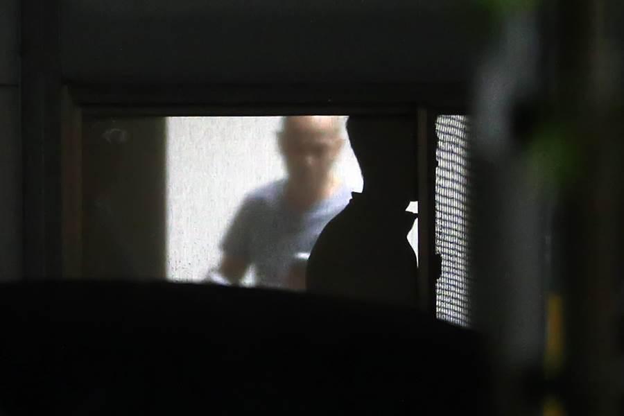 歹徒不時講電話、抽菸,也隨時往外看警方動向。(陳麒全攝)