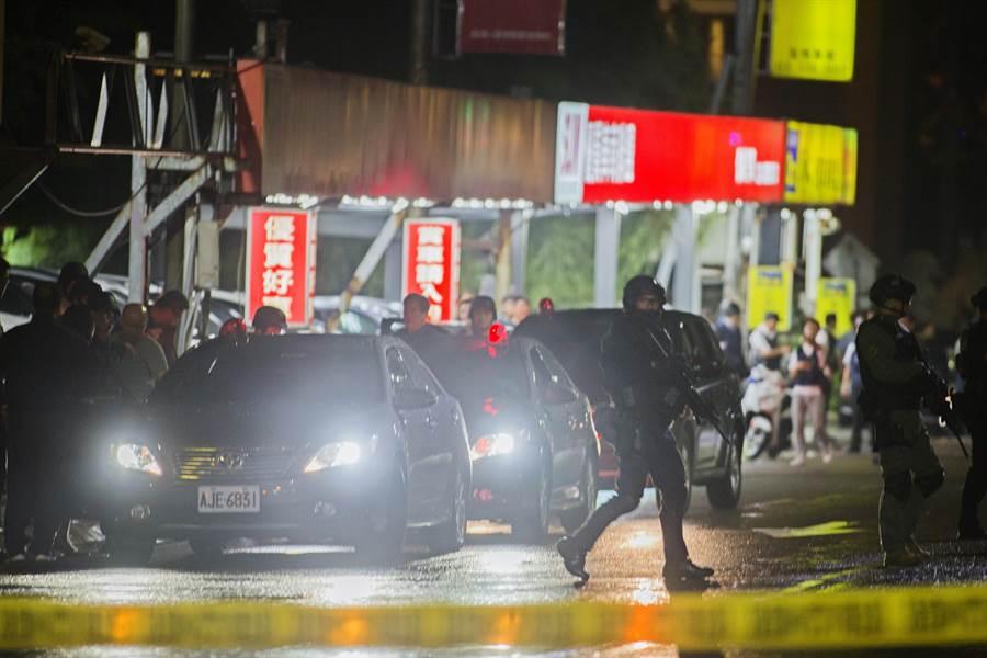 歹徒(左)於23時09分向警方投降,總共向警方交出2長槍3短槍,警方也拿著長槍在戒護下,將歹徒押往桃園市刑大偵訊。(陳麒全攝)