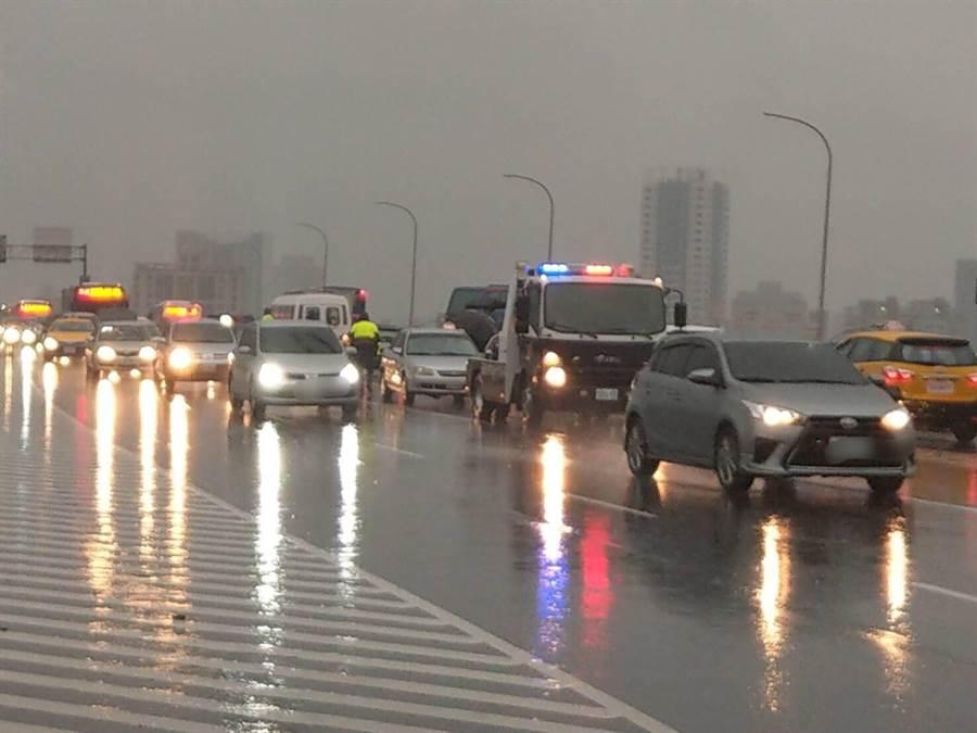 梅雨季節上下班常遇豪大雨,北市警冒雨疏導讓民眾免受塞車淋雨之苦。(吳家詮翻攝)