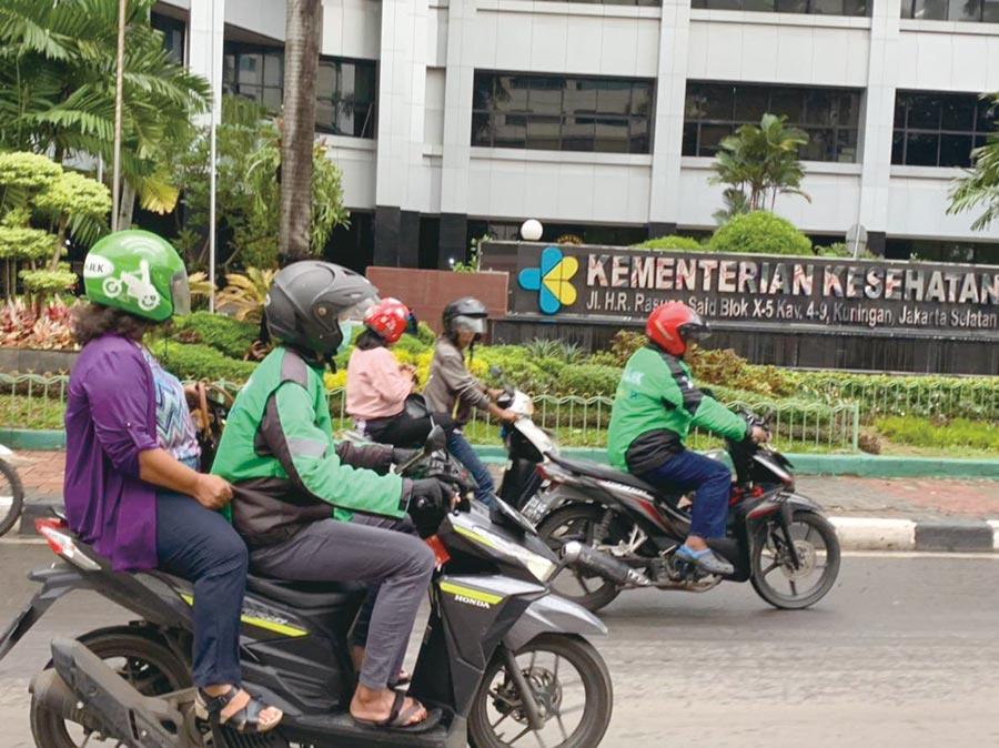 穿著綠色制服、戴著綠色頭盔的Go-Jek摩托車騎士。圖/劉季清