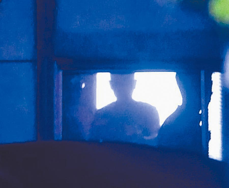 2名持槍歹徒挾持人質,並把人質推向窗戶處,防止警方狙擊手開槍。(陳麒全攝)
