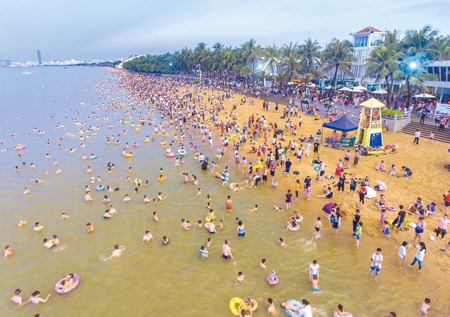 6月7日,逢端午節,海南海口市假日海灘景區匯集眾多民眾「洗龍水」。(中新社)