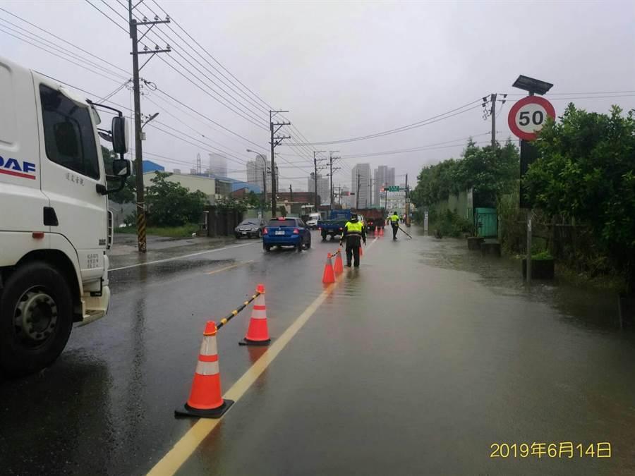 八德區大雨積水,警方在長興路、忠孝巷口交通管制。(甘嘉雯翻攝)