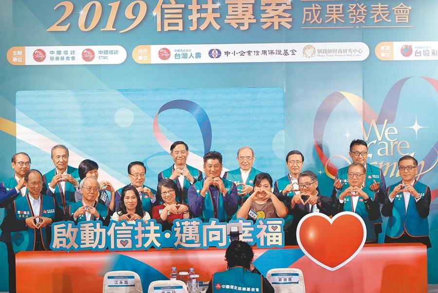 中國信託慈善基金會13日舉辦信扶專案成果發表會,董事長辜仲諒(前中)帶領來賓比出愛心手勢。(鄭任南攝)