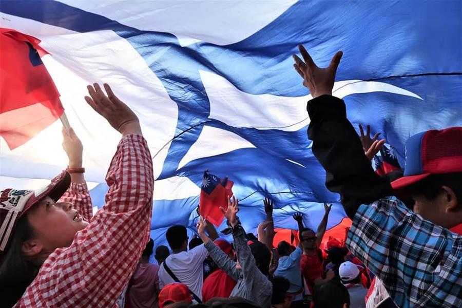 每次在造勢現場都會現身的超大型國旗下方,有韓家軍拍下感人畫面,眾人一心高舉雙手將「青天白日滿地紅」撐起,展現愛國意志。(陳正雄攝/韓國瑜鐵粉後援會)