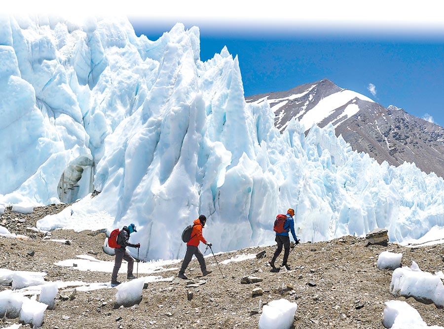5月21日,三名登山者行走在聖母峰海拔6000公尺左右的絨布冰川冰塔林間。(新華社)