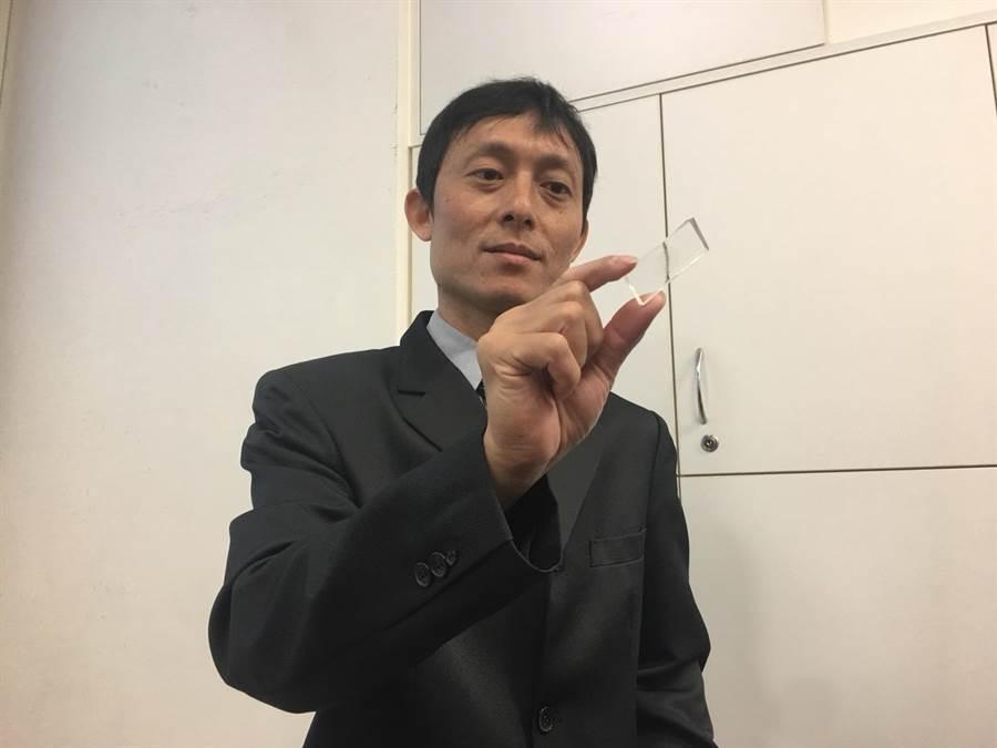 國衛院生醫工程與奈米醫學研究所副研究員許佳賢出示他所開發的晶片。(林周義攝)