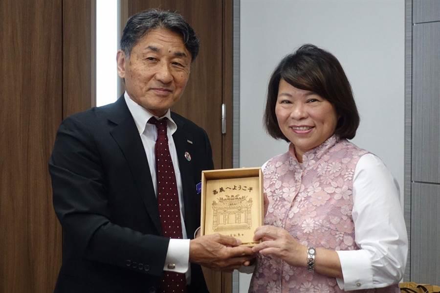 嘉義市長黃敏惠(右)赴日拚觀光,贈送檜木雕刻藝品「歡迎來嘉義」給日本旅行社社長。(嘉義市政府提供)