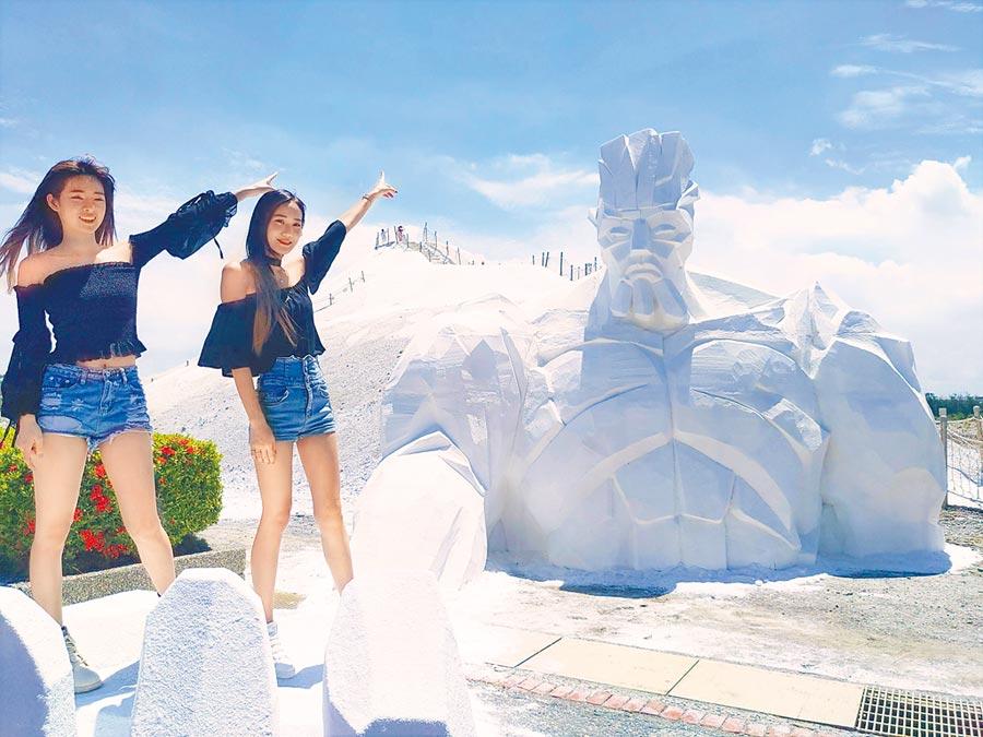 一見雙雕藝術季29日登場,遊客站在一座高5.5公尺、寬6公尺的「鹽巨人」手掌上拍照留念,相當吸睛。(莊曜聰攝)