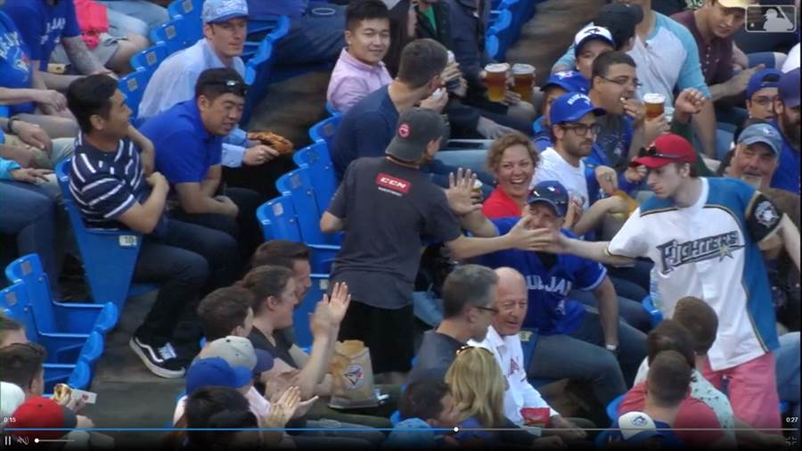 穿著日本火腿隊球衣的球迷,和撿到大谷翔平界外球的年輕球迷擊掌。(截自大聯盟官網)