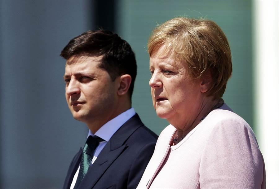 德國總理梅克爾(右)18日在迎接烏克蘭新總統澤倫斯基(左)時,身體忍不住不斷抽搐,全身顫抖得很厲害,她事後歸咎於脫水,不過英國醫生認為有可能是一種稱為「站立性顫抖」的症狀。(圖/美聯社)