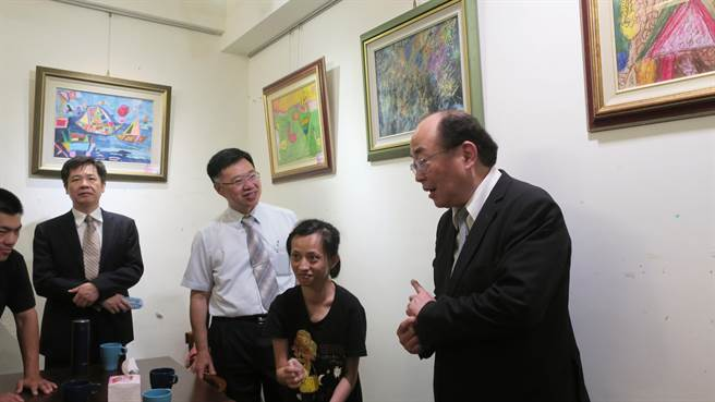 25歲的小怡(右2)向法務部保護司司長黃玉垣(右)和彰化地檢署檢察長徐錫祥(右3)介紹、解說自己的畫作。(謝瓊雲攝)