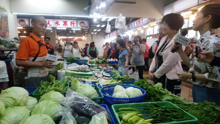 經發局長何怡明19日中午來到泰山公有市場,為暖心市集進行評分,阿美蔬果店老闆也現場講起「賣菜經」。(吳亮賢攝)