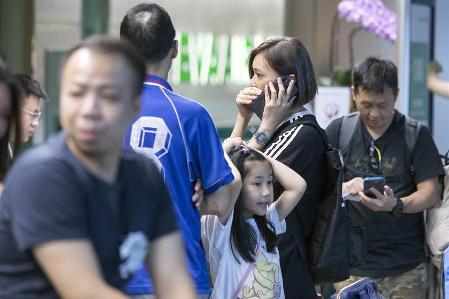 受影響旅客在長榮櫃台前焦急連絡親友。(陳麒全攝)