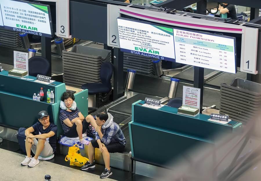 受影響的旅客無奈地坐在報到櫃台前等候。(陳麒全攝)