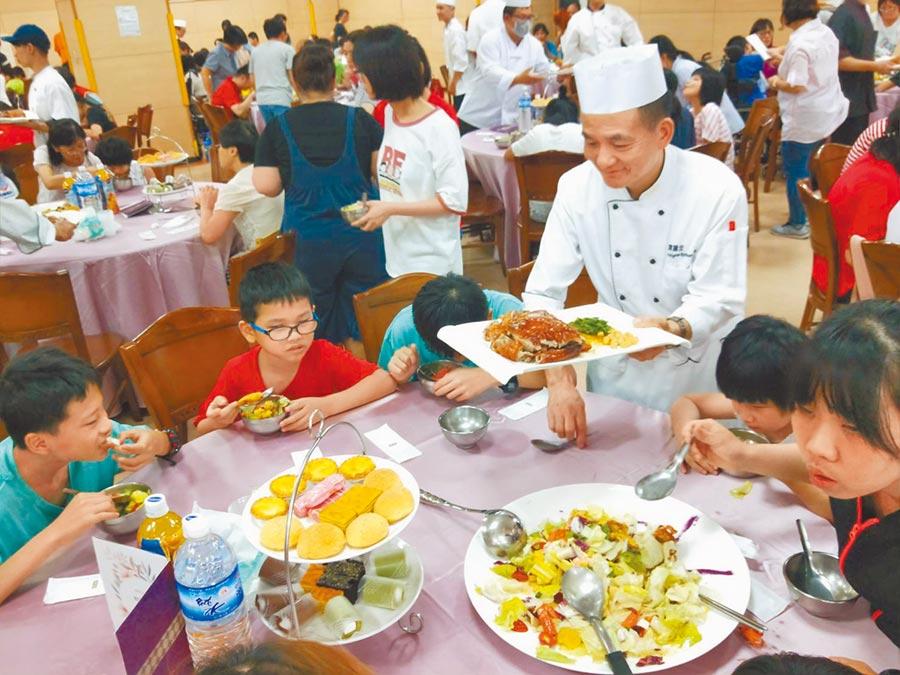 大廚進行桌邊服務,惠明盲童育幼院孩子開心享用佳餚。   (陳淑娥攝)