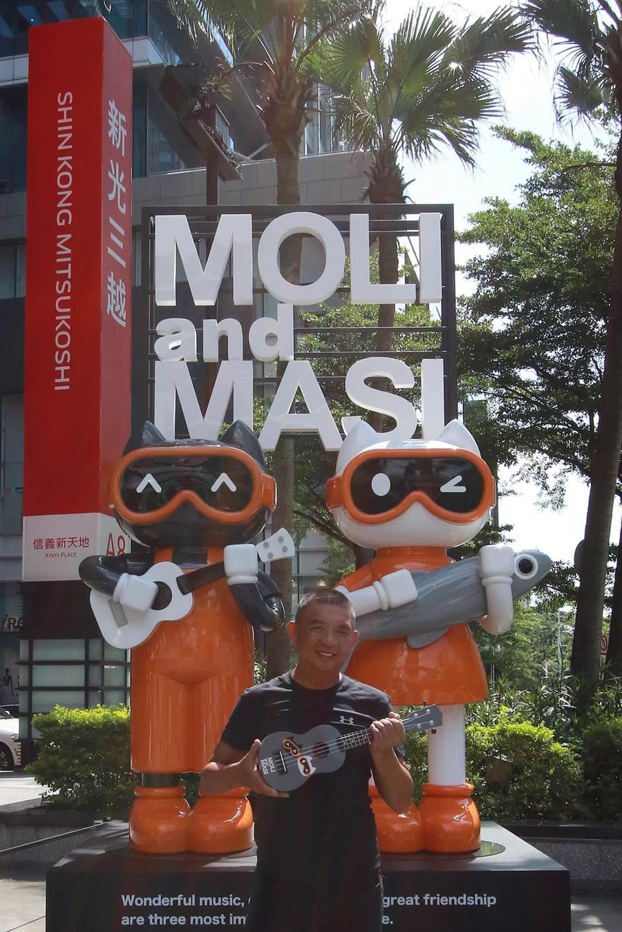 Akibo拿著「夏日愛音樂烏克麗麗」,在新光三越信義A8廣場與4.5米高的作品合影。抱著烏克麗麗、愛音樂的黑貓MOLI與帶著小魚抱枕、愛美食的白貓MASI,是Akibo生活的縮影。(新光三越提供)