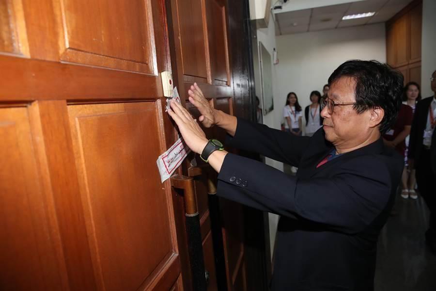 大考中心主任張茂桂給闈場大門上鎖,並貼上封條。(鄭任南攝)