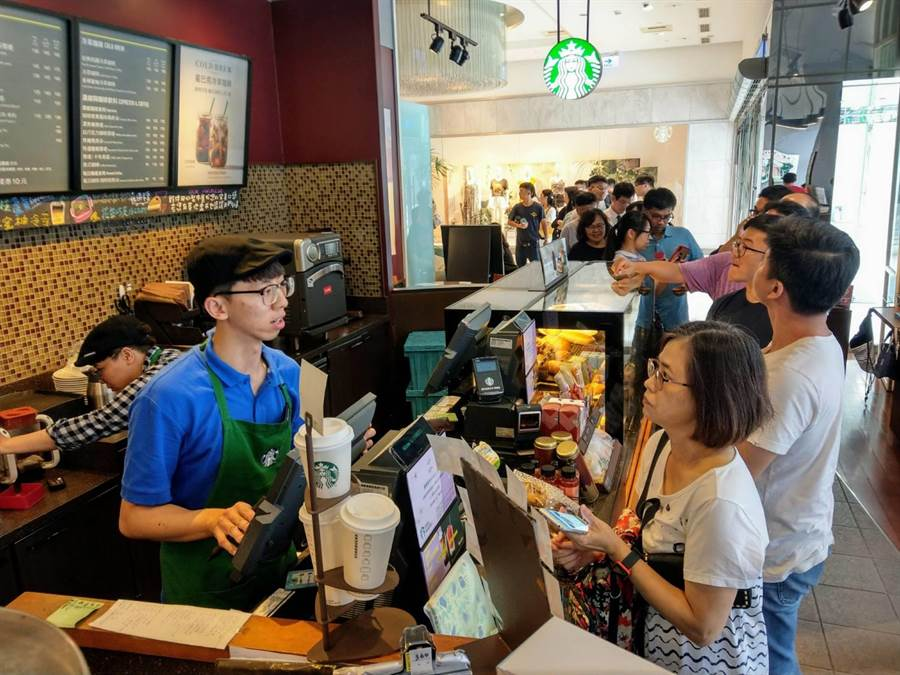 民眾紛紛自備容器配合宣導,在花蓮遠百星巴克咖啡店大排長龍,領取免費咖啡享用。(范振和攝)