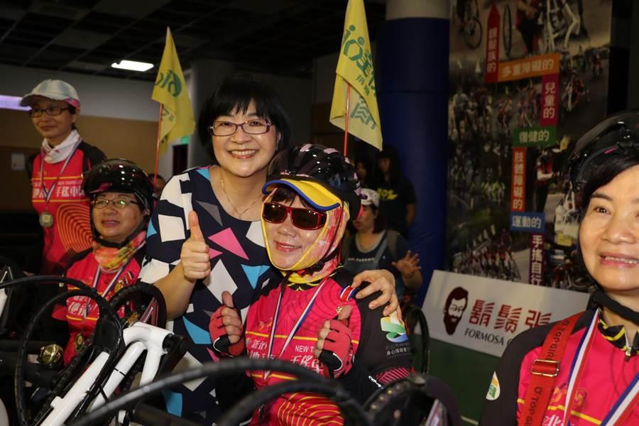 新北市10名身心障礙者利用手搖自行車進行環台傳愛,他們在12天內總共用手騎乘1088公里;新北市社會局長張錦麗(左三)為身障勇士頒贈完騎證明獎牌。(葉書宏翻攝)