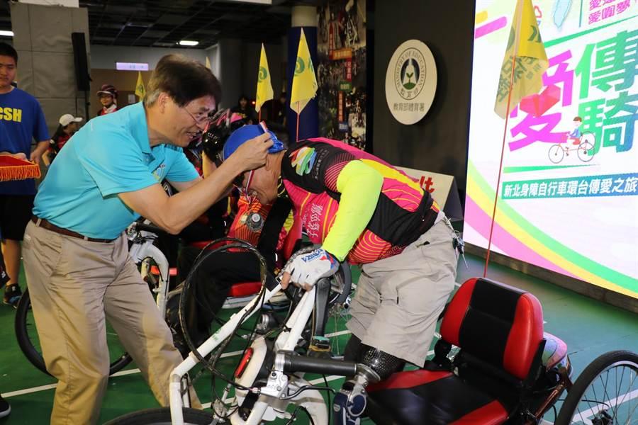 新北市10名身心障礙者利用手搖自行車進行環台傳愛,他們在12天內總共用手騎乘1088公里;教育部體育署長高俊雄(左)為身障勇士頒贈完騎獎牌。(葉書宏翻攝)