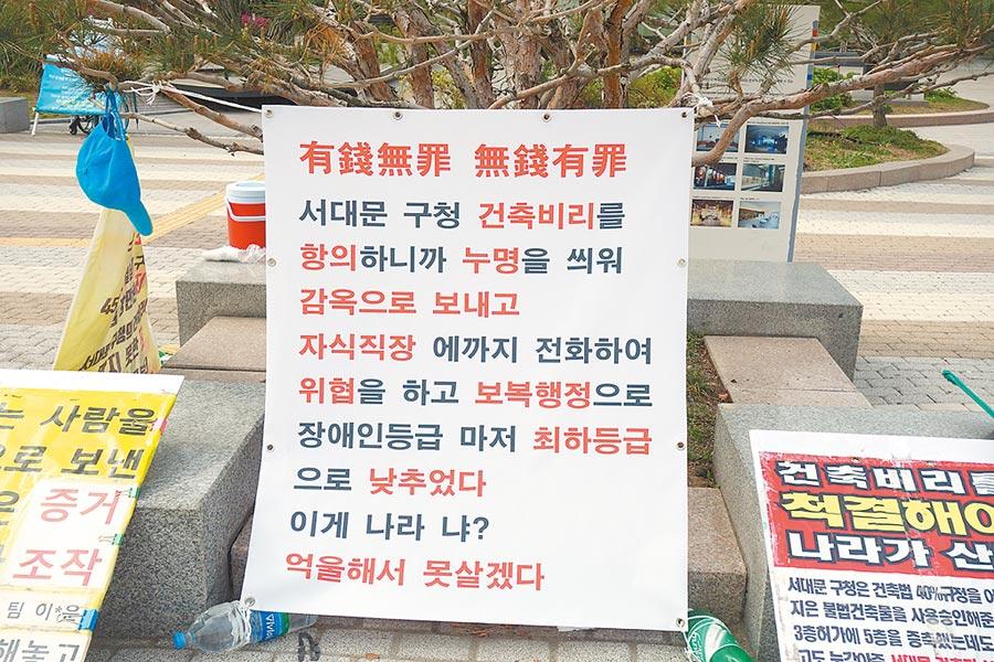 因開發弊案,而投訴無門者在青瓦台前控訴:「有錢無罪、無錢有罪」。圖/譚淑珍