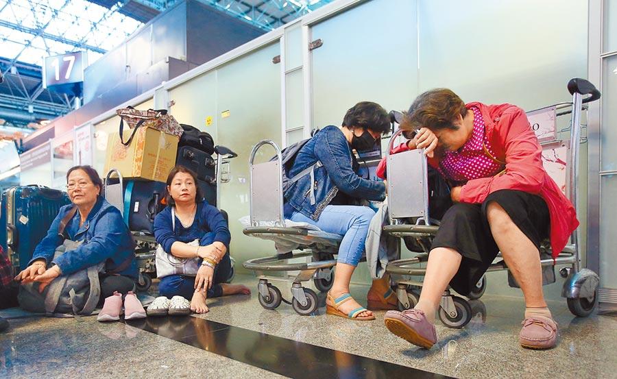長榮航空21日因罷工取消近半航班,不少在桃園機場枯等的旅客,累得就地休息。(范揚光攝)