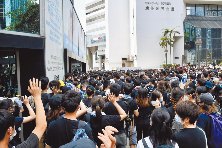 6月21日,大批示威者包圍香港灣仔稅務大樓,堵住各個出入口。(中新社)