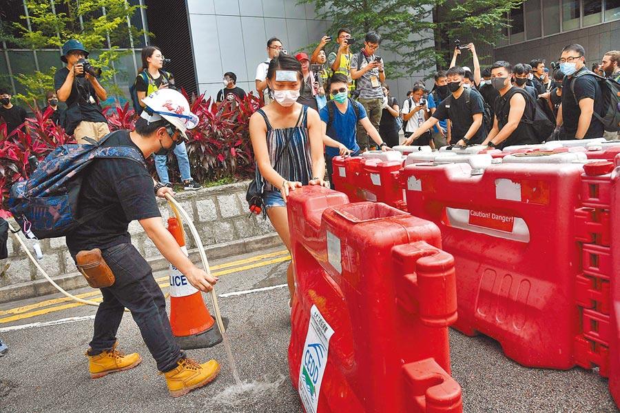 21日上午示威者前往警察總部用鐵馬等路障封鎖附近主要幹道。(中新社)