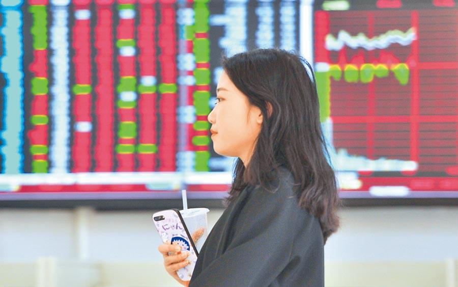 瀋陽一市民從股票大盤前經過。(中新社資料照片)