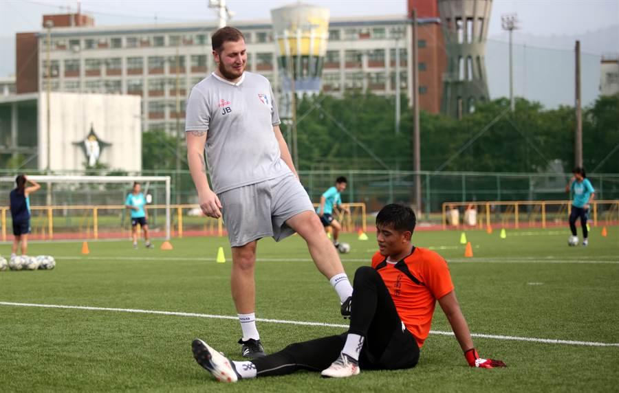 布拉辛頓(左)逗趣的踢了踢坐在地上喘氣的段昍。(李弘斌攝)