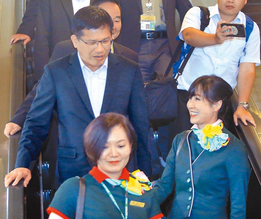 交通部長林佳龍(左)昨搭機返國,呼籲勞資雙方回到談判桌,且罷工預告期要更明確。圖為林佳龍在機場入境後與巧遇的長榮空服員寒暄。(范揚光攝)