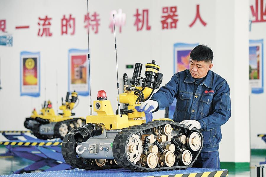 2018年12月12日,在福建寧德福鼎特種機器人生產基地,技術人員在保養一台組裝完畢的消防機器人。(新華社)