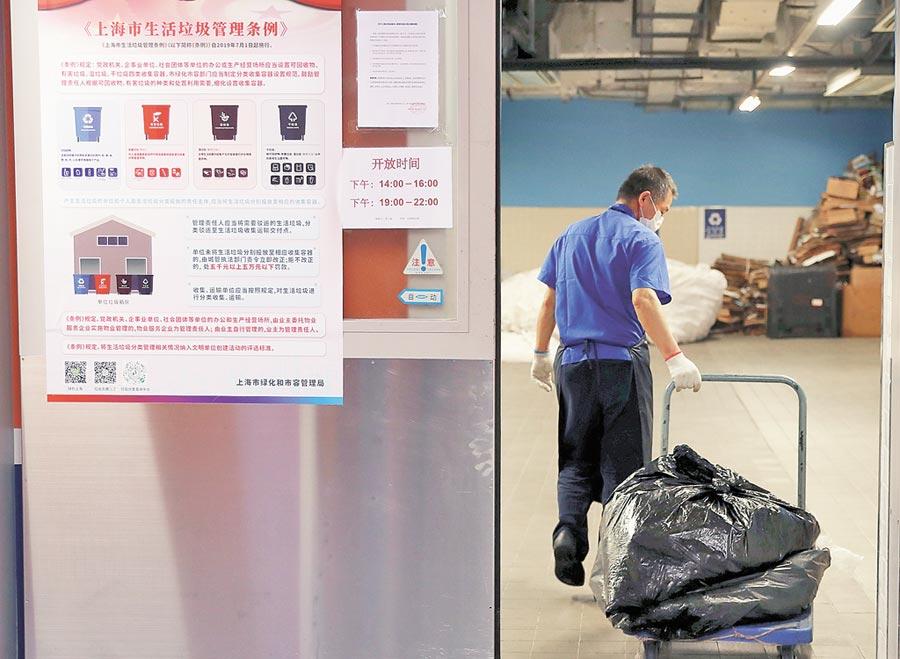 《上海市生活垃圾管理條例》7月1日正式施行,圖為垃圾回收人員進行集中分類整理。(新華社)