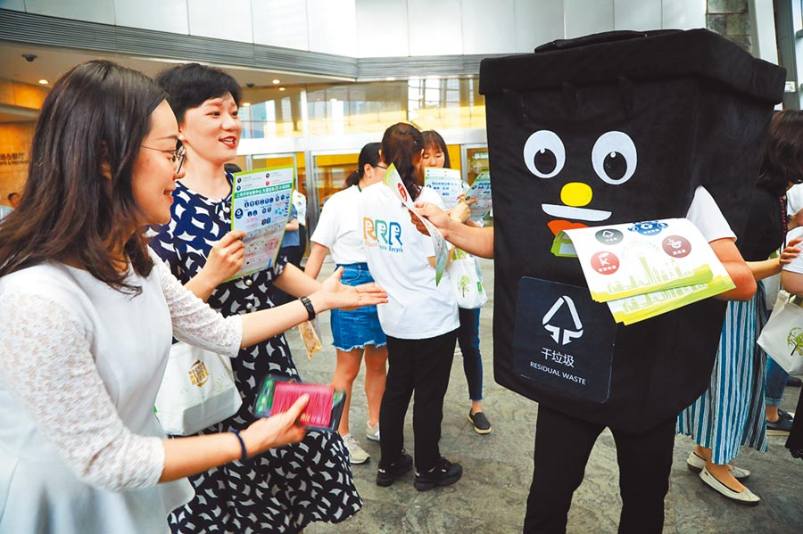 上海環球金融中心19日利用午休時間向白領們宣講垃圾分類知識。(中新社)