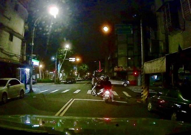 興隆所員警以機車擋住車流,協助老婦過馬路,被後方開車民眾拍下整個過程。〔謝明俊翻攝〕