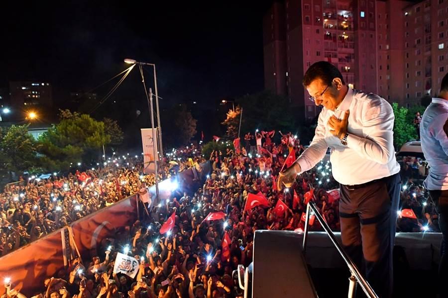 當選伊斯坦堡市長的在野黨候選人伊瑪莫魯23日投票結束後在舞台上對支持群眾說話。(圖/美聯社)