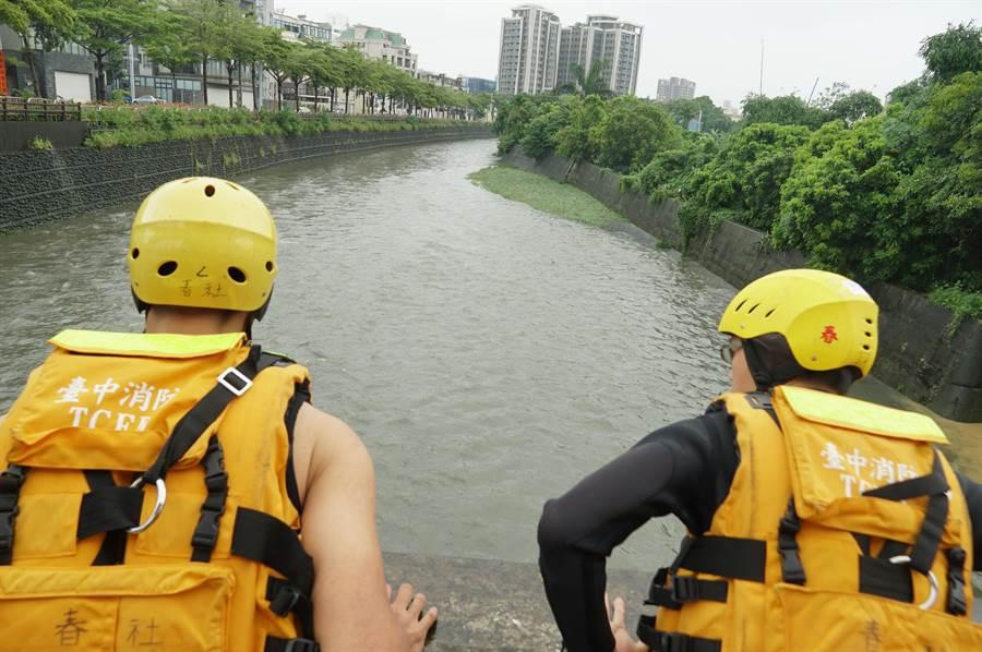 傳男子23日晚墜落南屯溪中遭沖走,24日搜救人員持續往下游搜尋,二位消防人員,從橋上眺望,搜尋可疑漂流物。(黃國峰攝)