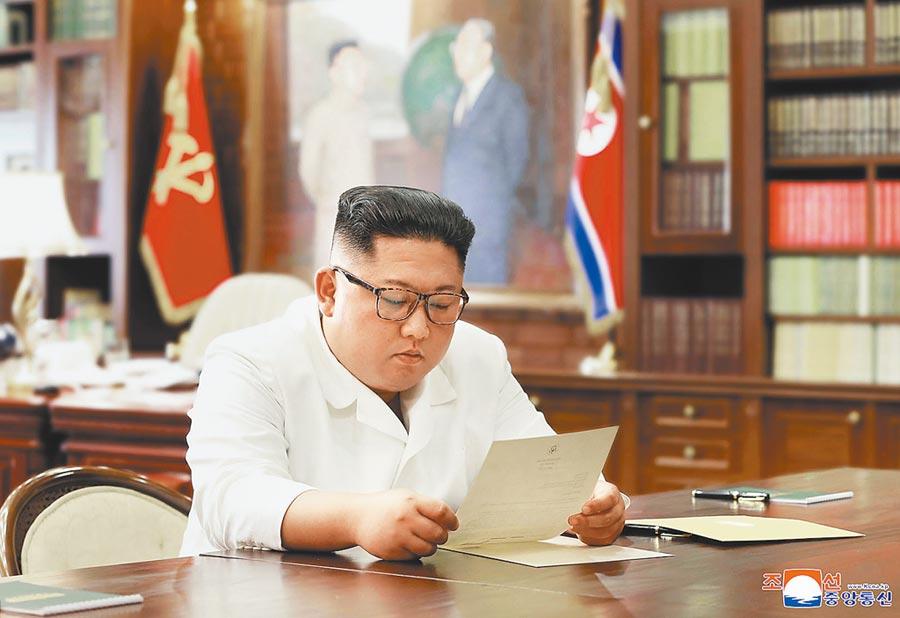 北韓領導人金正恩正在看美國總統川普來信,確實日期與內容不明,只能從右下角浮水印「KCNA」看出照片是朝中社提供。(美聯社)