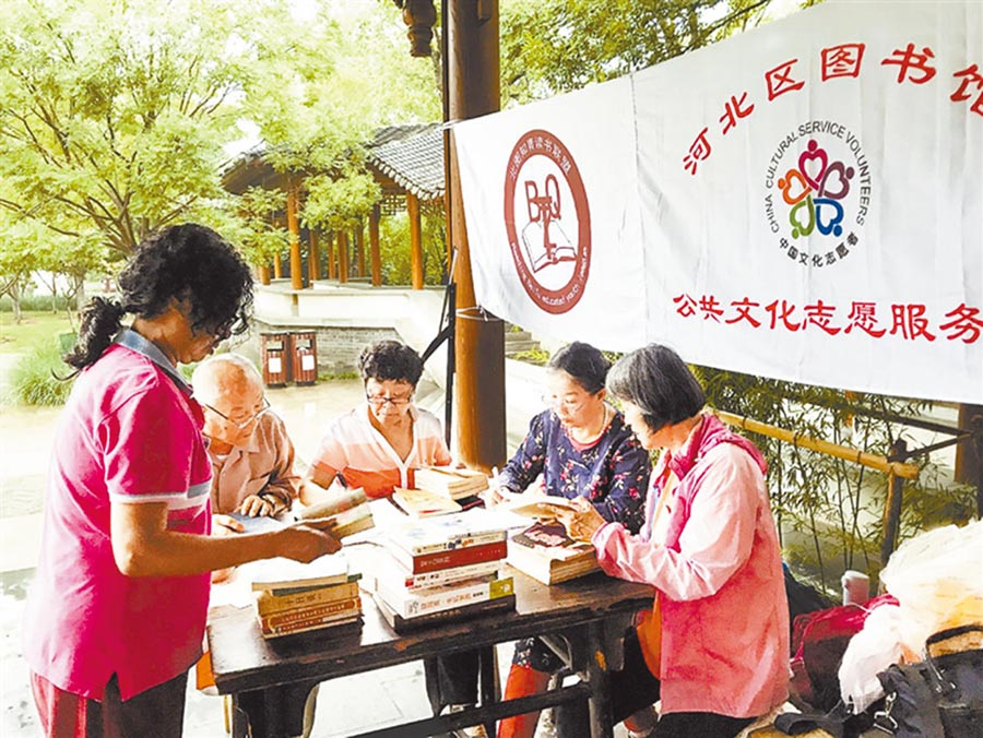 天津河北區南普公園「換書角」,圖書館公共文化志工服務隊的隊員在整理圖書。(曹雪攝)