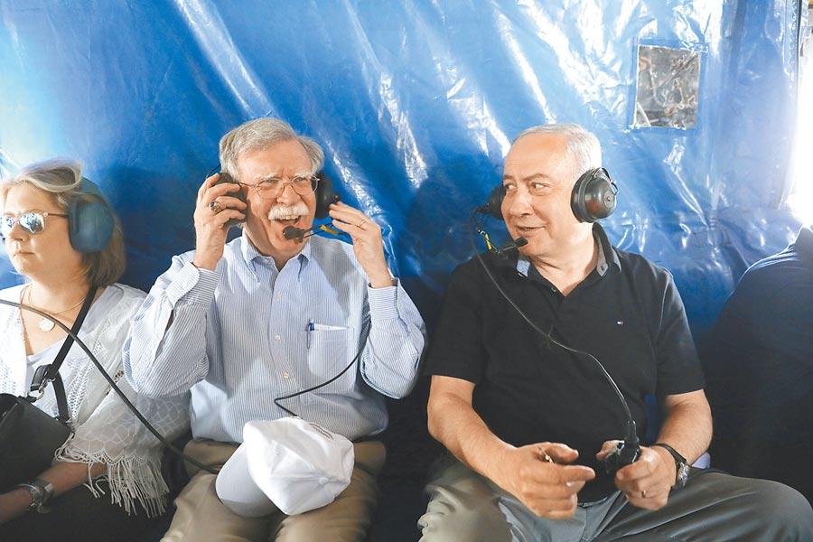 白宮國安顧問波頓(左)23日與以色列總理納坦雅胡(右)一起搭乘直升機,飛經約旦河?#21462;?#20234;朗外長指控2人是所謂「B隊」成員,企圖設局令川普向伊朗開戰。(美聯社)