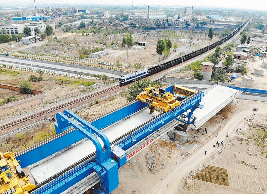 大陸地方債發行量創近3年新高,加碼基建。圖為6月16日,大型機械在河南焦作架設箱梁。(新華社)