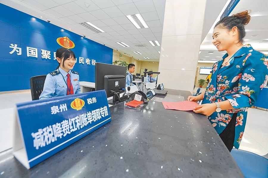 4月19日,福建納稅人領到稅務局工作人員送上的減稅降費紅利帳單。(新華社)