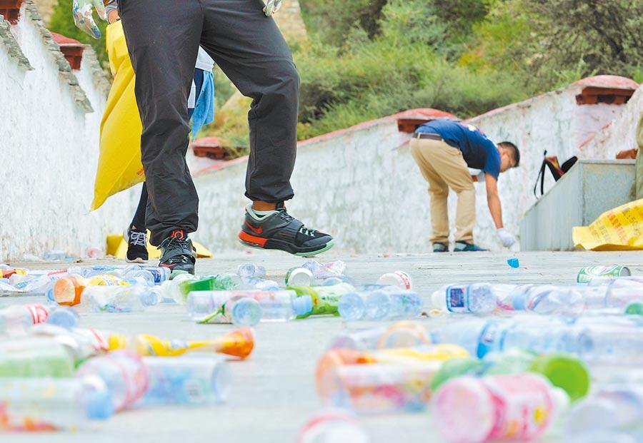環保志工在撿拾人們丟棄的垃圾。(新華社資料照片)