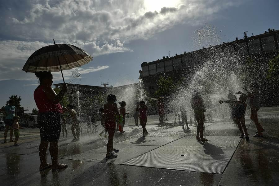 歐洲遭到熱浪襲擊,本周起將有多地達到攝氏40度至45度高溫,預計許多國家的歷史高溫記錄將被打破。圖為西班牙龐羅納市因高溫難耐,兒童聚集到噴泉戲水消暑。(圖/美聯社)