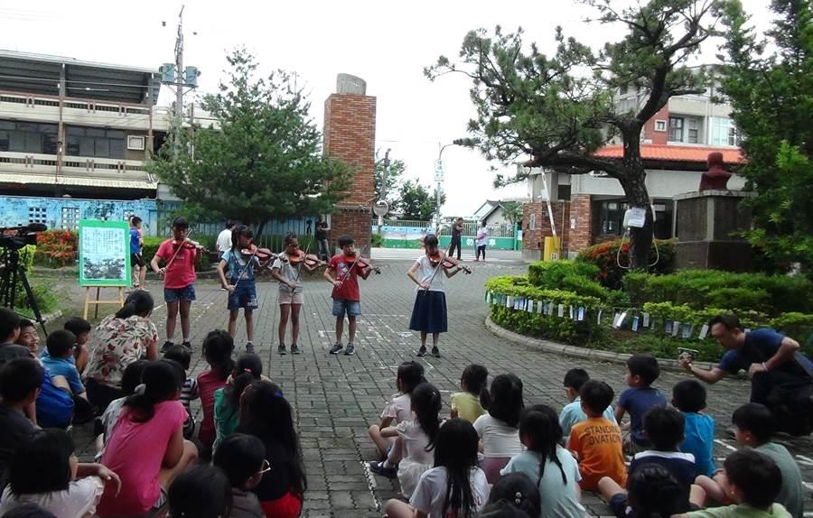 26日永興學童們齊聚大樹下演奏小提琴和烏克麗麗,引來返校的老校友們陣陣掌聲,歡樂的氣氛,慶祝老樹在治療後重獲新生。(謝瓊雲攝)