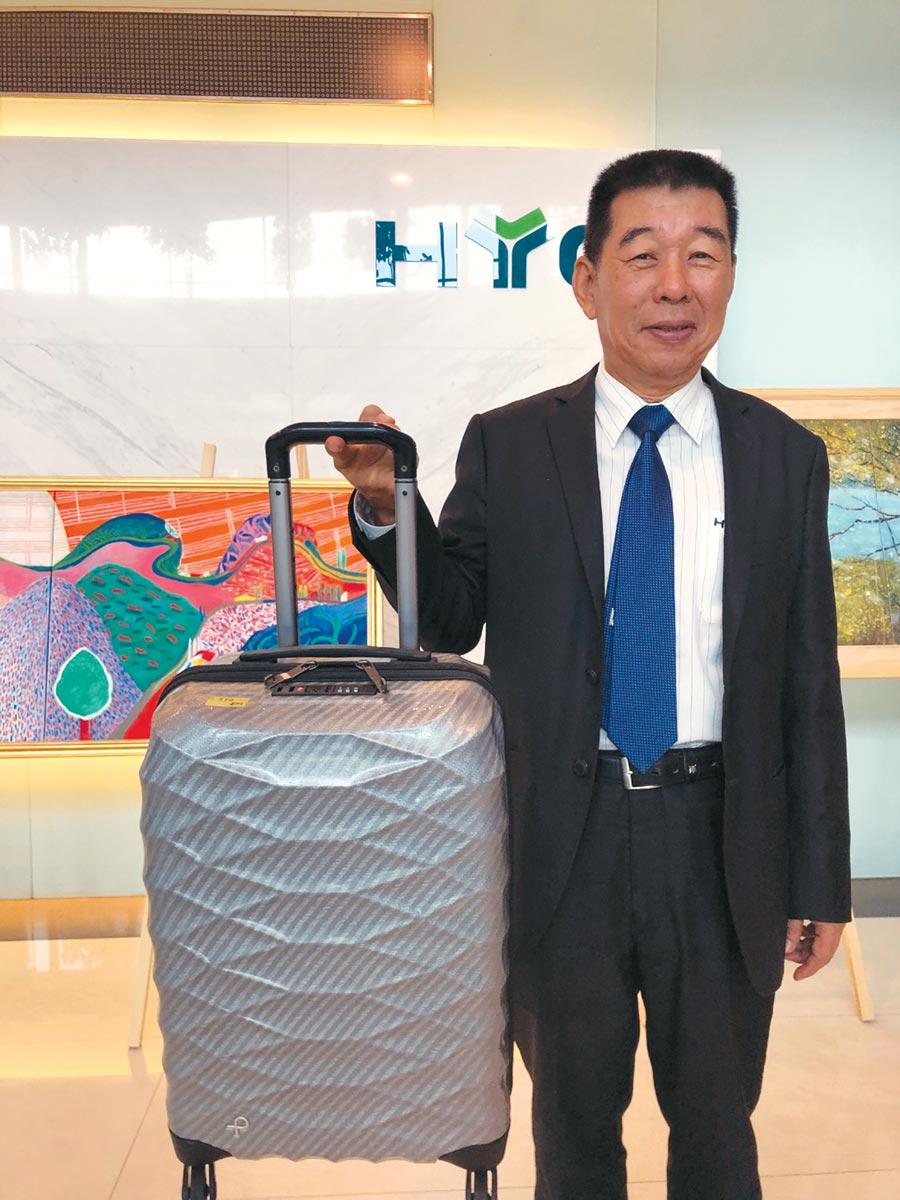 鑫永銓董事長林季進,以單手食指舉起全球最輕的日本ACE公司品牌行李箱。圖/劉朱松
