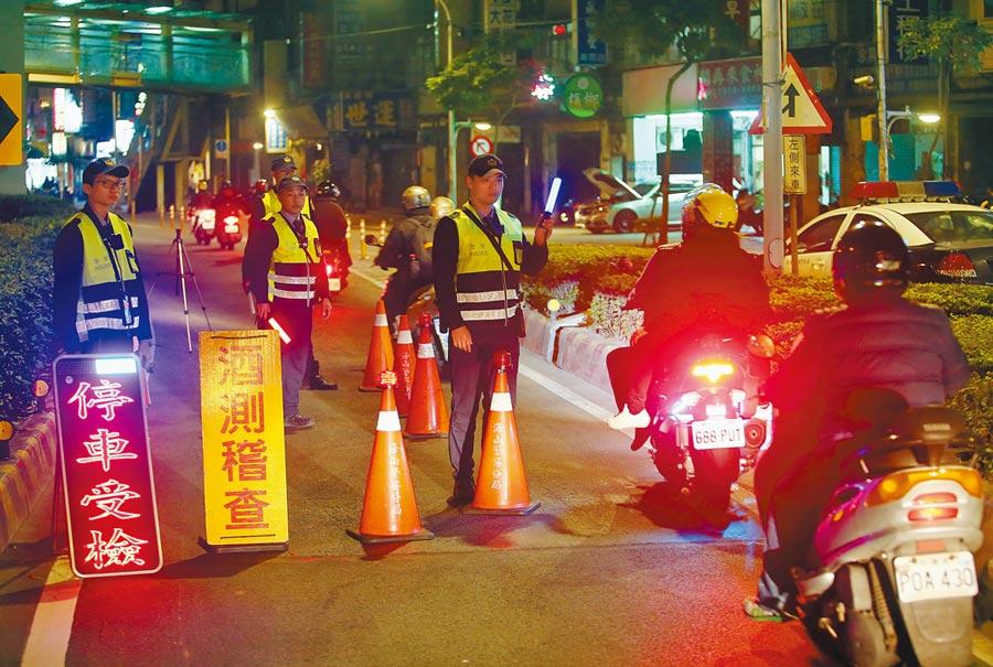 酒駕罰責新制下周一上路,汽機車駕駛酒測濃度超過0.25毫克,同車乘客也要受罰。圖為員警在市區橋梁實施酒測臨檢勤務。(本報資料照片)