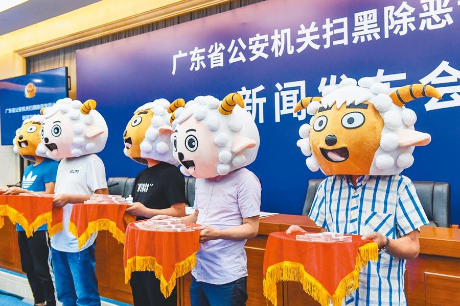 5月14日,5名男子戴喜羊羊頭套在廣東省公安廳領取舉報涉黑惡犯罪獎勵金。(中新社)